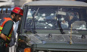 Emergency services examine an army jeep  after it was attacked by gunmen in Islamabad, Pakistan