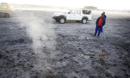 Workers near a smoke plumefrom an underground fire in Las Tablas de Daimiel national park in Spain
