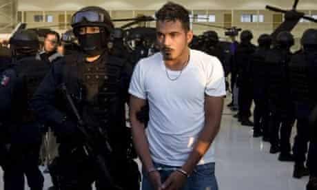 A Mexican federal police officer escorts Jose Roberto Sanchez 'El Chivo', 24, suspected member of the Michoácan cartel known as La Familia