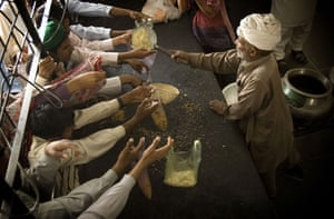 Environment decade: Men hold plastic bags for food distribution at a mosque in Lahore, Pakistan