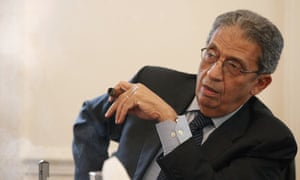 Arab League Secretary General Amr Moussa smokes a cigar as he addresses a conference in London.