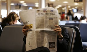 A commuter reads The Wall Street Journal while waiting for his flight
