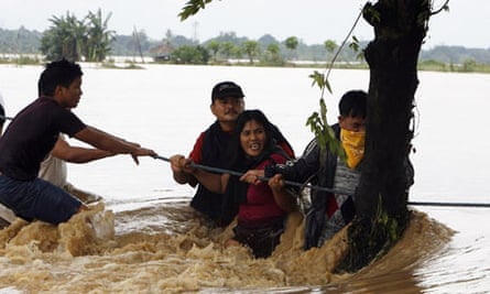 Survivors hold onto a rope while crossing a flooded road in Rosales Pangasinan, Philippines