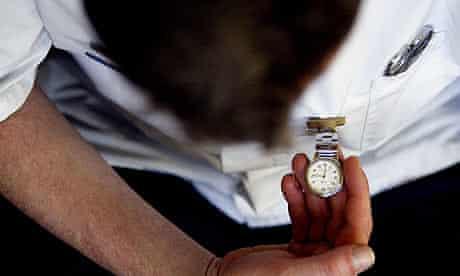An NHS nurse checks his fob watch