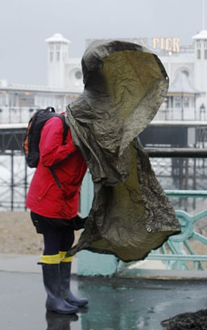 UK gales: A woman's poncho blows over her head as she walks on Brighton seafront