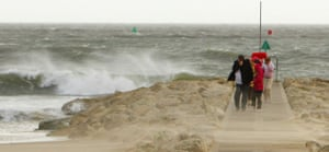 UK gales: A family shields itself from the wind and sand at Sandbanks