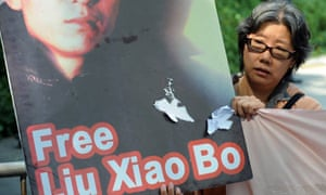 A protestor holding a picture of Chinese writer Liu Xiaobo marches to the US consulate in Hong Kong