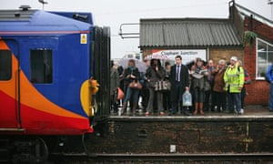 Commuters wait to squeeze on to the next train to at Clapham Junction station in London.