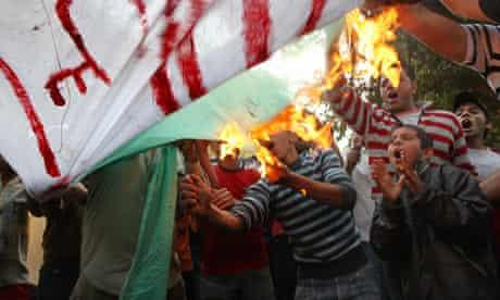 Egyptians burn an Algerian flag outside the Algerian embassy in Cairo