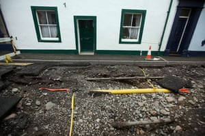 Cockermouth floods: Pipes are exposed on a damaged road as flood water recedes in Cockermouth