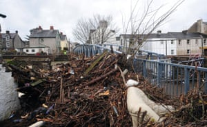 Cockermouth clear-up: Debris piled up against a closed footbridge after flood water receded