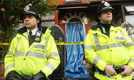 Police stand outside a house in Manchester after counter-terrorism raids