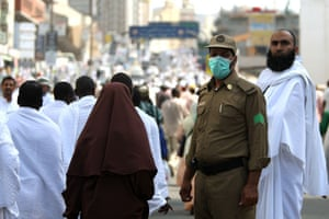 Mecca Hajj: A Saudi security official wearing a protective mask watches Muslim pilgrims