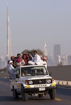 Eid al-Adha: People load-down a vehicle as they pass the Burj Dubai tower