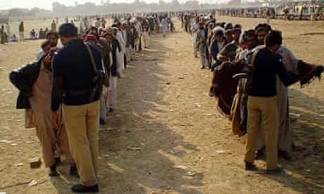 Pakistani police search displaced people at a camp in in South Waziristan.