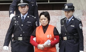 Xie Caiping is led from court after her sentencing in China's Chongqing municipality.