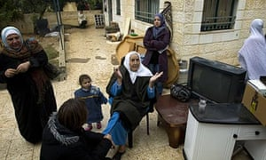 A Palestinian woman gestures as she sits in front of the disputed house in east Jerusalem