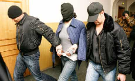 Alleged killer Eugenia Khasis, in a black hood, is led by police to  court in Moscow.