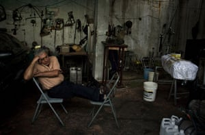 Guatemala morticians: A mortician takes an afternoon nap in his mechanic shop turned funeral home