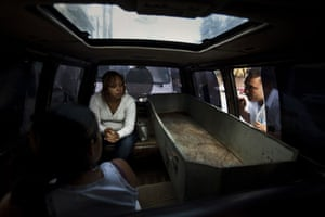 Guatemala morticians: A funeral salesman explains paperwork to the relatives of a murder victim