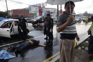 Guatemala morticians: A funeral salesman waits at a crime scene for the arrival of relatives