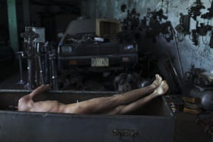 Guatemala morticians: A corpse lies in a box as morticians take a break from embalming him
