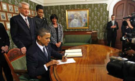 Barack Obama signs the guestbook at the Nobel Institute watched by dignitaries and the press
