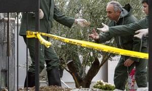 Police officers investigate Tassos Papadopoulos's grave