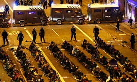 Arrested demonstrators sit on the ground as they are surrounded by police in Copenhagen.