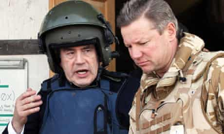 Gordon Brown wears a helmet and body armour as he leaves 'Little Heathrow' at Kandahar airbase