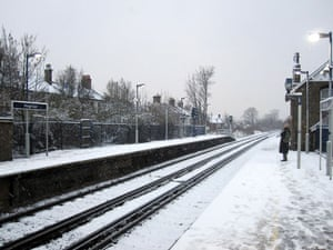 Snow in the UK: A lone commuter in the morning snow at Penge East Station, South London