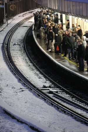 Snow in the UK: Commuters wait for a train at East Croydon railway station in south London