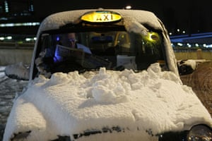 Snow in the UK: A snow covered taxi waits for a fare at East Croydon railway station