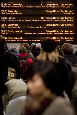Snow in the UK: Rail passengers look at the departures screen in Kings Cross station