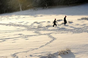 Snow in the UK: People walk through the snow in Knole park, Sevenoaks, Kent