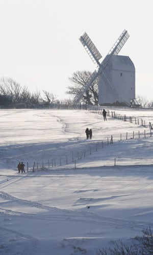 Snow in the UK: People walk in the snow in front of the Jill windmill at Clayton
