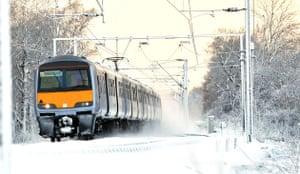 Snow in the UK: A train travels through the snow near Ingatestone, Essex