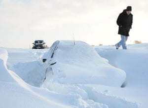 Snow in the UK: A man walks past an abandoned car buried in a snow drift near Royston