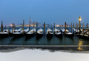 Snow around the world: Snow-covered gondolas moored in Venice's lagoon, Italy