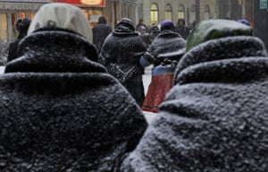 Snow around the world: Budapest, Hungary: Women wearing traditional clothes walk during snow fall