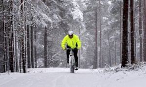 Snow around the world: Scotland: A man cycles up a path in the Cairngorm mountain range