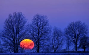 Snow: Germany: The sun sets behind snow-covered trees near Breckerfeld