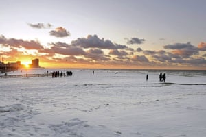 Snow: Belgium: The beach of Oostende is covered with snow at sunset