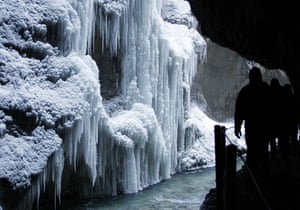 Snow: Germany: Hikers walk past huge icicles in the Partnachklamm canyon