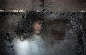 Snow: Bulgaria: A woman looks through an icy window on a tram in Sofia