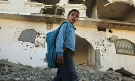 Palestinian boy walks past a damaged house in Beit Lahiya