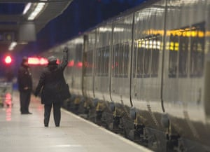 travel chaos: A guard waves off the first Eurostar train to Paris after cancellations
