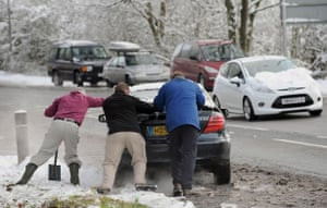 Travel chaos: Three men attempt to push a car from the side of the road in Basingstoke