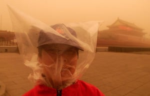 2002-03: 2002, Beijing: A woman covers her head with a plastic bag in a sandstorm
