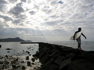 24 hours: A surfer walks with his surfboard on Waikiki Beach in Honolulu, Hawaii